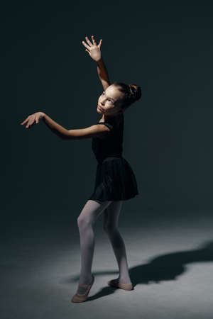 Beautiful girl ballerina dancing in light play and shadowson dark background Standard-Bild