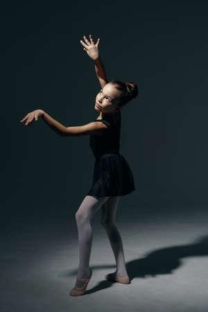 Beautiful girl ballerina dancing in light play and shadowson dark background Reklamní fotografie
