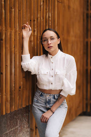 Fashion portrait of an attractive brunette with straight hair. Girl dressed in a white blouse and glasses posing on a stylish background from vertical boards