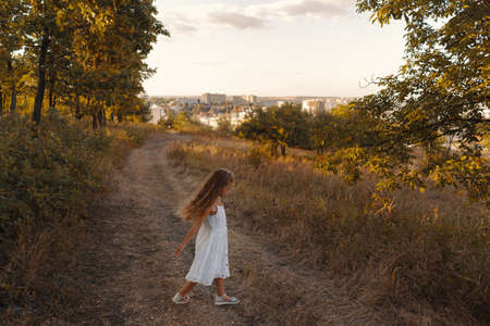 Lovely carefree little girl wearing white clothes enjoy the day and sunshine rays while playing in the nature