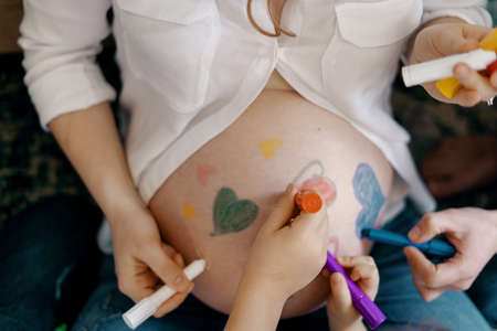 Lovely family drawing hearts on moms tummy expecting a new baby to come in their happy life.