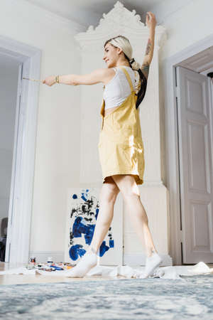 Cheerful dancing girl in a white space with a painting in background in yellow sunny clothes and white socks