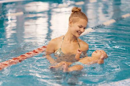 Jeune maman et son bébé profitant d'un cours de natation pour bébés dans la piscine. Enfant s'amusant dans l'eau avec maman
