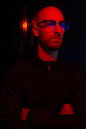 Close up portrait of hairless man wearing glasses, beard with red neon light reflected on his face sitting in the dark