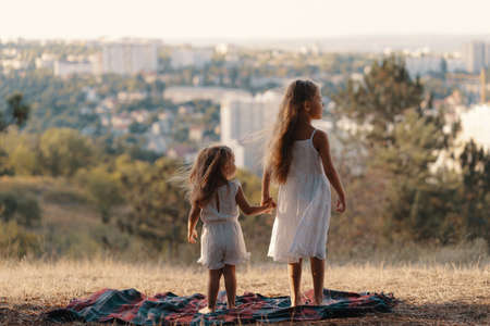 Two little sisters in white clothes standing on a blanket watching the city while resting in nature