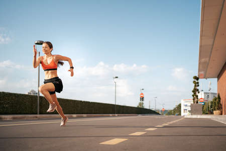 Young woman sprinting in the morning outdoors. Side view of female runner working out in the city with sky in background Stock Photo