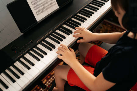 Young boy sitiing at digital piano. Playing keyboard, focused kid have activity at home. Hobby