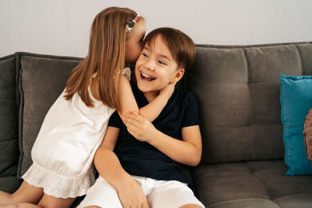 Girl whispers boy in the ear a secret. Childrens gossip Banque d'images