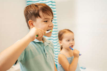 Indoor portrait of cute kids brushing their teeth in the bathroom, happy family and dental hygiene Stock Photo