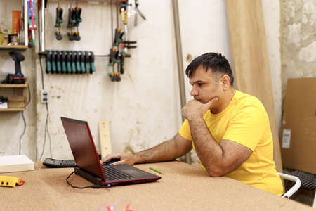 Carpenter in yellow T-shirts using laptop while designing furniture in workshop with instruments on the table in the background