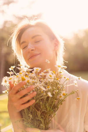 Portrait of a Sunny woman embracing a bunch of chamomile with the sun rays on her face enjoying life Stock Photo