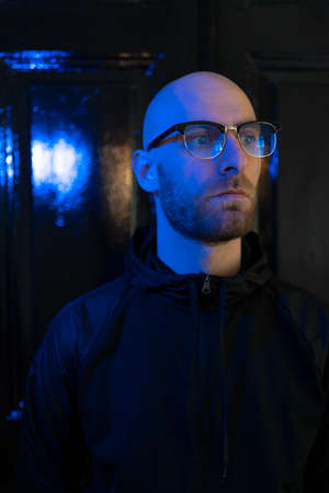 Close up portrait of hairless man wearing glasses, beard with blue neon light reflected on his face sitting in the dark