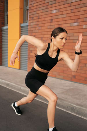 Young woman sprinting in the morning outdoors. Female runner working out in the city. 스톡 콘텐츠