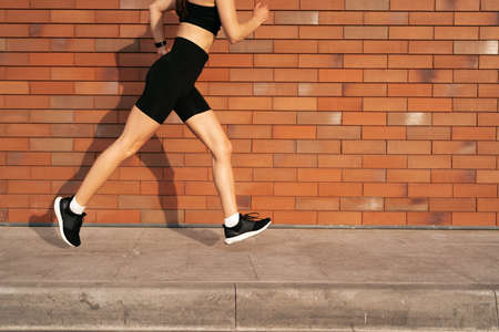 Young woman legs running on sidewalk in morning over brick wall. Health conscious concept. Healthy active lifestyle. Active girls jogging together on road in the city.