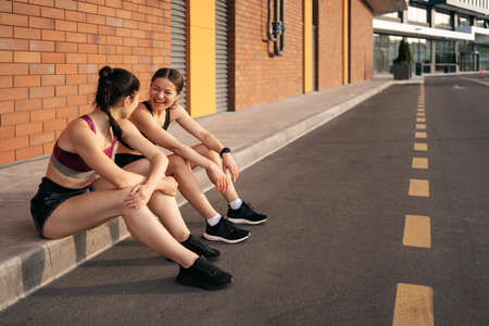 Two women before urban workout. Girls preparing for running and sitting in the street. Fitness break 스톡 콘텐츠 - 154754943