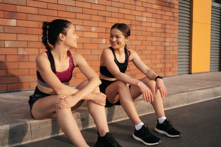 Two women before urban workout. Girls preparing for running and sitting in the street. Fitness break