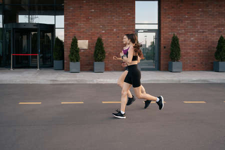 Young woman running on sidewalk in morning. Health conscious concept. Healthy active lifestyle. Active girls jogging together on road in the city. 스톡 콘텐츠 - 154754949