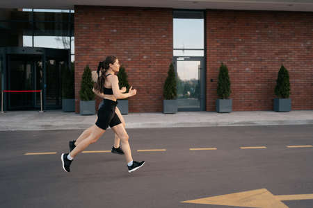 Young woman running on sidewalk in morning. Health conscious concept. Healthy active lifestyle. Active girls jogging together on road in the city.