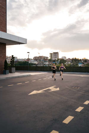 Young woman running on sidewalk in morning. Health conscious concept. Healthy active lifestyle. Active girls jogging together on road in the city. 스톡 콘텐츠 - 154754955