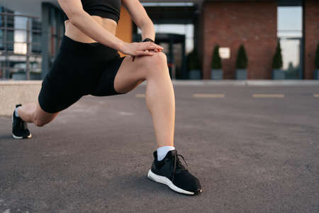 Athlete woman preparing for running on the city street. Legs warming and stretching. Sport tight clothes. Horizontal. 30s