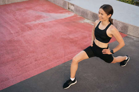 Athlete woman preparing for running on the city street. Legs warming and stretching. Sport tight clothes. Horizontal. 30s 스톡 콘텐츠 - 154754960