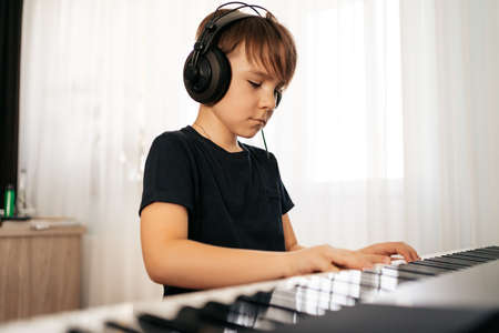 Young boy sitiing at digital piano. Playing keyboard, focused kid have activity at home. Hobby 스톡 콘텐츠 - 154754962