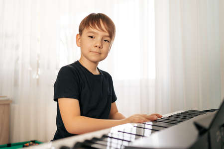 Young boy sitiing at digital piano. Playing keyboard, focused kid have activity at home. Hobby 스톡 콘텐츠 - 154755404