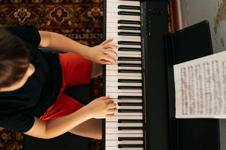 Young boy sitiing at digital piano. Playing keyboard, focused kid have activity at home. Hobby 스톡 콘텐츠 - 154755405