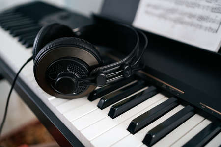Electronic piano or synthesizer with black headphones close-up. Music devices.