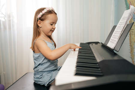 Lovely little girl sitiing at digital piano. Playing keyboard, focused kid have activity at home. Hobby