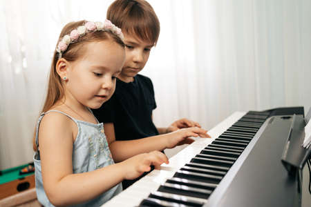 Boy and girl sitiing at digital piano. Playing keyboard, focused kid have activity at home. Hobby 스톡 콘텐츠
