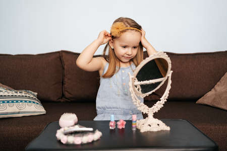 Little girl at home sitting on sofa arranging her hair using beauty accessories looking at the mirror