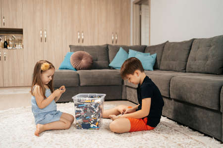 Funny, cute girl and boy playing  at home on the floor, first education role lifestyle 스톡 콘텐츠 - 154755503