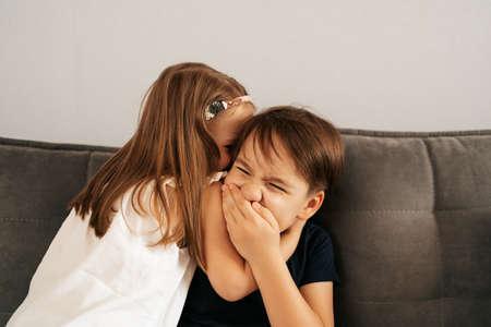 Girl whispers boy in the ear a secret. Childrens gossip 스톡 콘텐츠 - 154756125