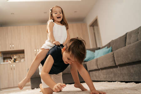 Cheerful boy and girl playing at home. Brother carries on his back, his happy sister 스톡 콘텐츠