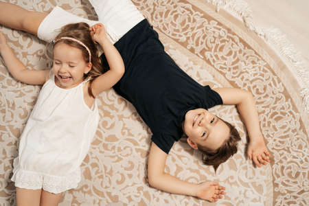 Adorable boy and girl lying on the cream carpet at home, top view. Cheerful siblings 스톡 콘텐츠
