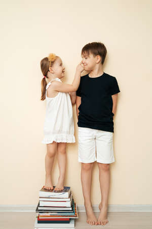 Brother and sister measuring their height near home wall