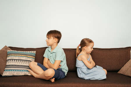 Brother and sister sit back to back on the couch upset at each other Stock Photo