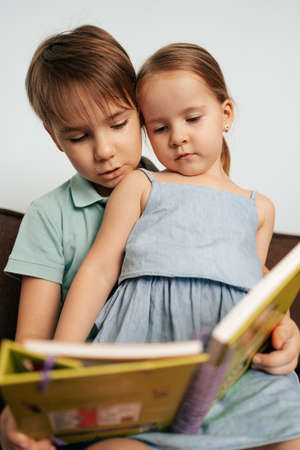 Bigger brother teaches his little sister to read while staying at home together 스톡 콘텐츠