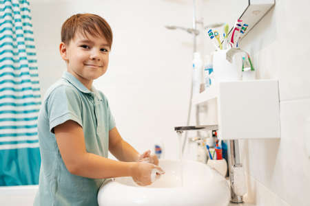 Preschool smiling boy Washing hands with soap under the faucet with water. Clean and Hygiene concept. 스톡 콘텐츠 - 154756172