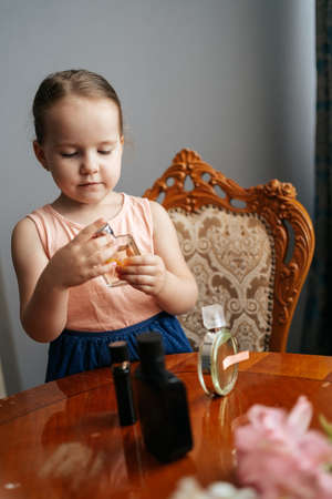 The ingenious little girl has a big dream to become a perfumer. She sits at home at a table with the bottles of perfume, smelling the aromas, making notes with her senses and ingredients Stok Fotoğraf