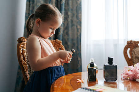 The ingenious little girl has a big dream to become a perfumer. She sits at home at a table with the bottles of perfume, smelling the aromas, making notes with her senses and ingredients 스톡 콘텐츠 - 154756177