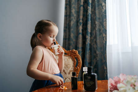 The ingenious little girl has a big dream to become a perfumer. She sits at home at a table with the bottles of perfume, smelling the aromas, making notes with her senses and ingredients 스톡 콘텐츠