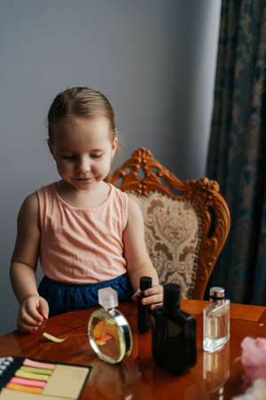 The ingenious little girl has a big dream to become a perfumer. She sits at home at a table with the bottles of perfume, smelling the aromas, making notes with her senses and ingredients 스톡 콘텐츠 - 154755573