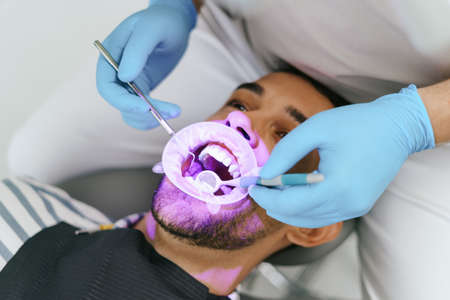 Young man with patient bib on a dental chair, pink light oriented on his teeth and a dentist who sits next to him wearing blue medical gloves while examining oral cavity Stock Photo