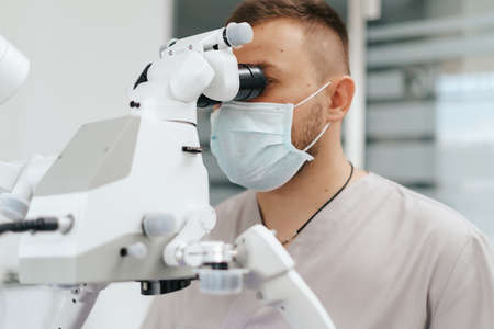 Young man with patient bib on a dental chair and a dentist who sits next to him. He looks on his teeth using a dental microscope and holds a dental bur and a mirror. 스톡 콘텐츠 - 154755585