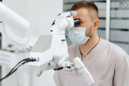 Young man with patient bib on a dental chair and a dentist who sits next to him. He looks on his teeth using a dental microscope and holds a dental bur and a mirror. 스톡 콘텐츠