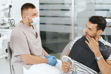 Male Dentist discussing with happy patient after treatment 스톡 콘텐츠