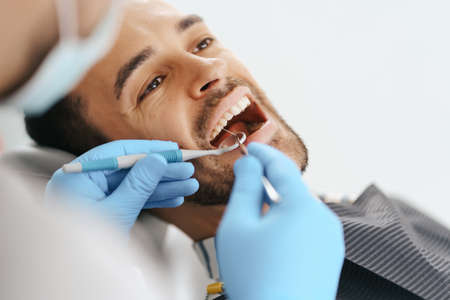 Smiling young man sitting in dentist chair while doctor examining his teeth 스톡 콘텐츠