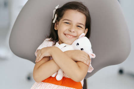 Little happy cute girl with beautiful smile sitting in dentist chair holding a white soft toy